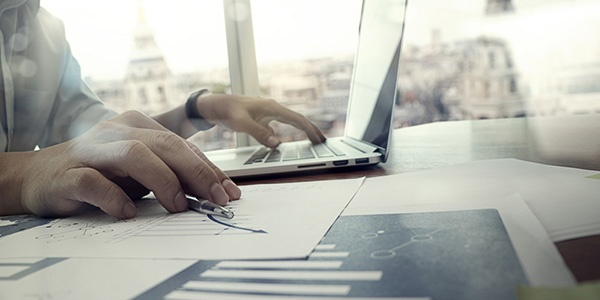 business documents on office table with laptop computer and graph financial diagram and man working in the background.jpeg